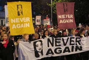 """Protestors marching in Dublin with pictures of Savita Halappanavar and the slogan """"Never Again"""""""